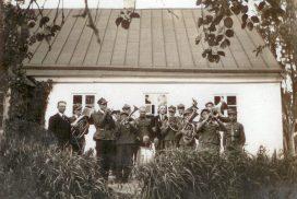 Orkiestra kościelna przed budynkiem plebanii w Raczkach. W składzie orkiestry mieszkańcy Małych Raczek. Lata 30. XX wieku.